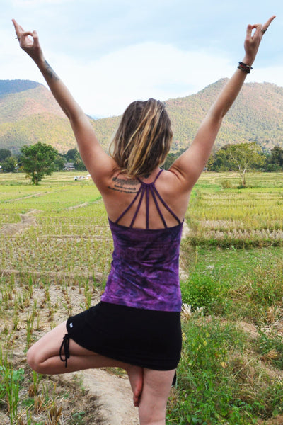 Back view Purple Haze Tie Dye Shanti Tank Top by Lotus Tribe Clothing with built in bra and stunning back strap design shown on woman in tree pose paired with Onyx Cinch Skirt.