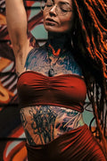Strapless Bandeau Top with puckering between the breast in solid Rust color. Shown on tattooed model with matching dreads and shorts.