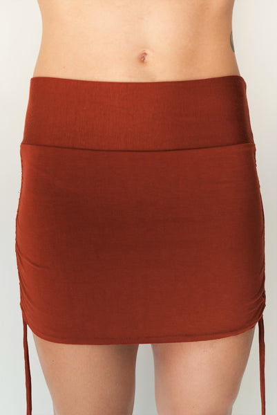 Cute little rust colored mini skirt with pull strings on the sides and fold over waist for adjustable fit. Soft and comfortable 90% rayon 10% cotton. Fits S/M