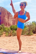 Woman in yoga pose wearing Sky blue Yoga Shorts and matching Trinity Bra in the desert