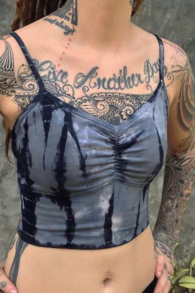 Side view of Sodalite tie dye Blissed Out crop tank with adjustable spaghetti straps and scrunched center puckering between the breasts. Steel blue with black streaks and white highlights. 90% Organic cotton with 10% spandex