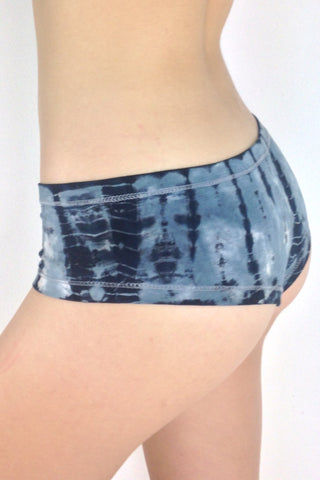 Side view of Sodalite Tie Dye Cheeky Undies, blue grey tie dye with black and white highlights 90% cotton 10% spandex with small lotus flower embroidery detail on left leg