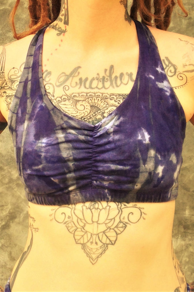 Front view of shakti Sportsbra in Wildflower tie dye is a full coverage bra with scrunching between the breasts in cool purple hues with grey streaks and white highlights.