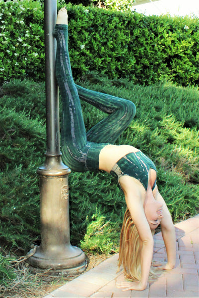 Yoga woman doing yoga pose in yoga pants with matching Sports Bra. Organic cotton Rainforest tie dye is multi green hues and beige highlights.