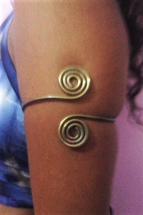 Double swirl, one on top and one on bottom from each side of brass armband.