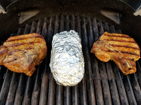 pork chops and a baked potato wrapped in aluminum foil