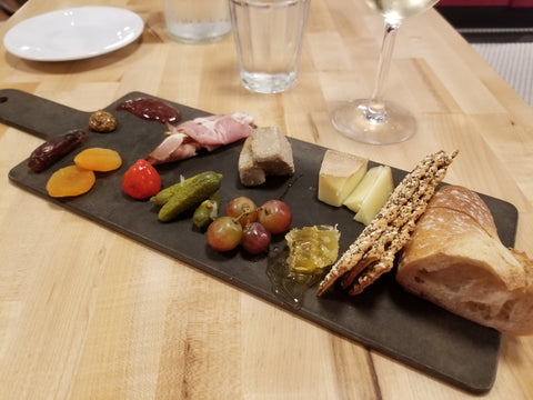 Serving board with bread, cheese, meats and other foods.