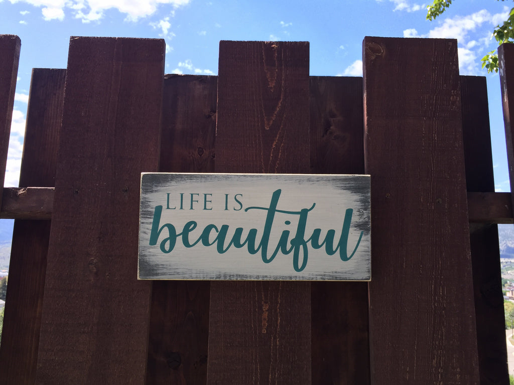 Life is Beautiful sign on pine