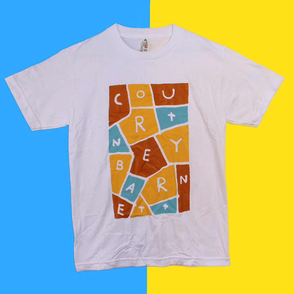 Courtney Barnett white T-shirt with blue, brown, beige letters.