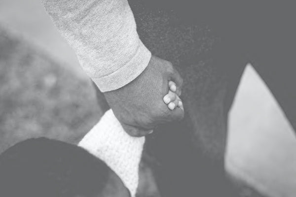 close up of Father and infant son holding hands