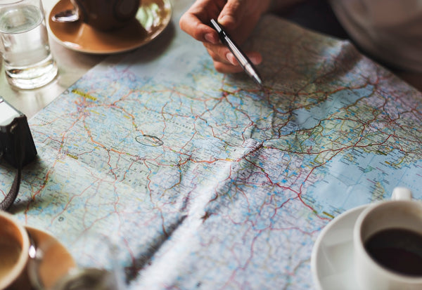 Jack Dusty CLothing and Lifestyle blog - Mans hand planning a roadtrip on a map with a coffee.