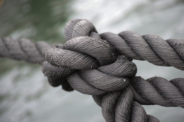 Jack Dusty Clothing & Lifestyle blog - Heavy weathered rope tied in a big knot in focus and the sea in the background.