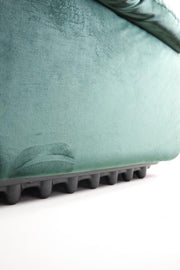 Green velvet armchair with protective plastic base