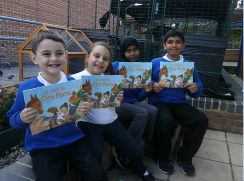 Four Chalkhill primary school students holding up a copy of the book each