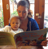 Little girl reading A visit to City Farm picture book with auntie