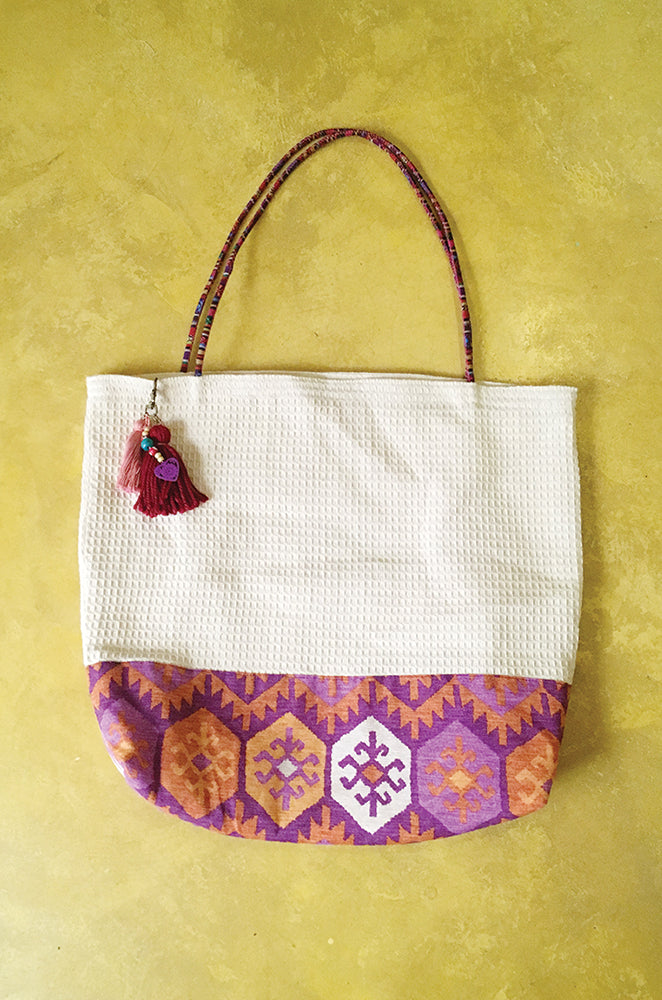 woven cotton bag with tassel charm