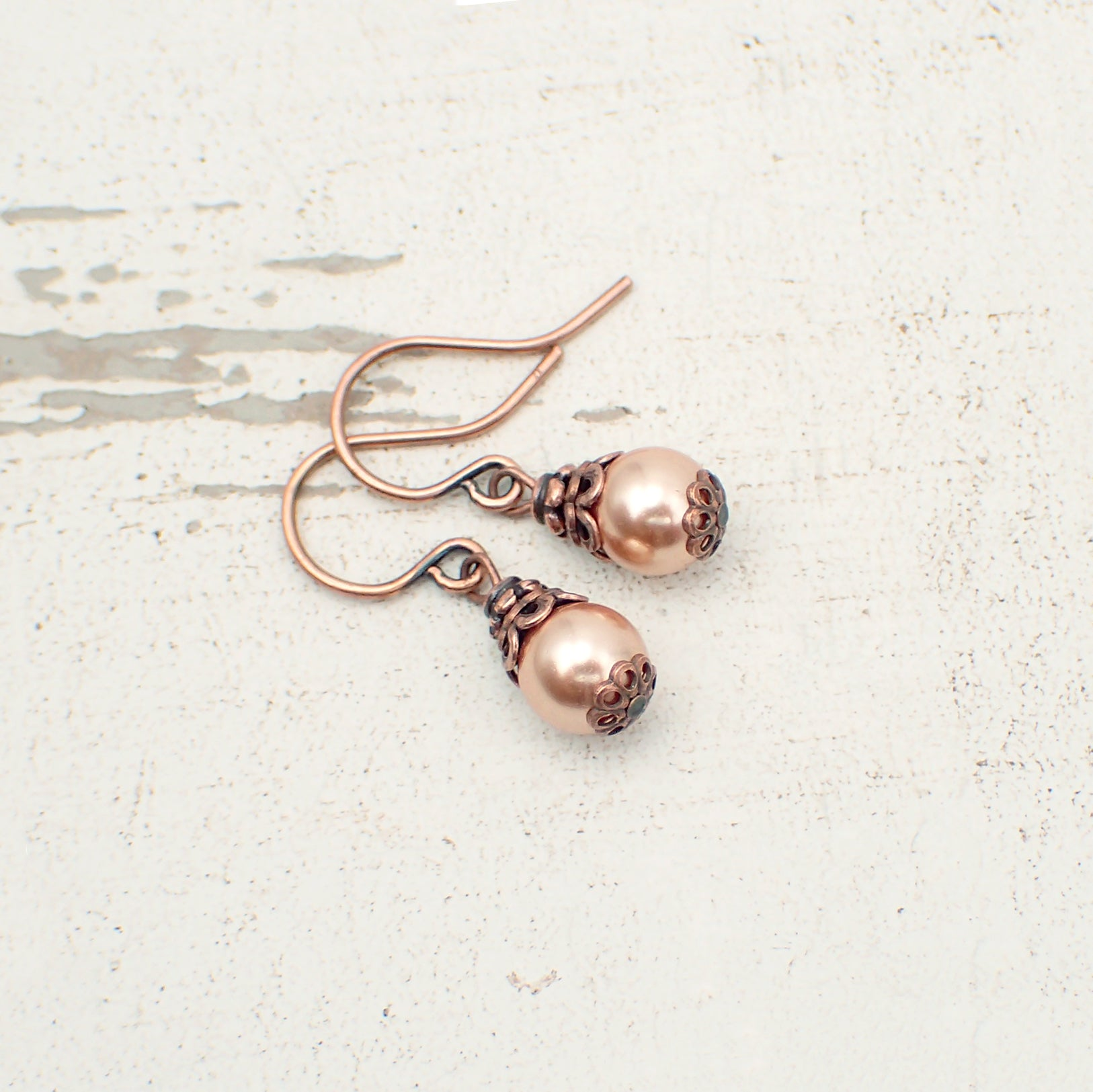 Dainty little rose gold-colored Swarovski crystal pearls dressed with antiqued copper details.