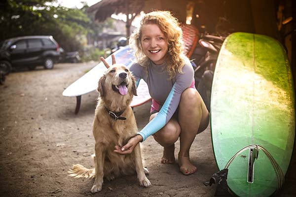 surfing dog women getting ready to surf with dog.jpg