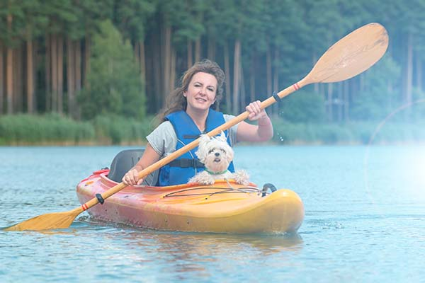 woman kayaking with dog
