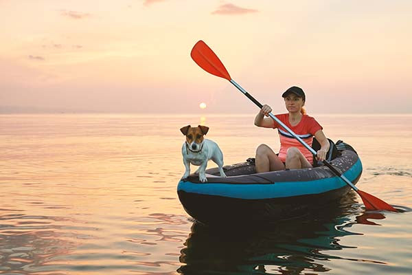 woman kayaking with jack russel dog at sunset