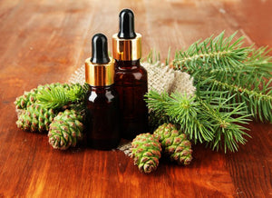 Oil bottles on a wooden table nestled in fir cones