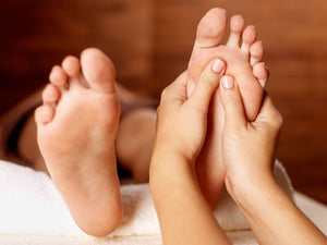 Close up of a massage therapist's hands whilst they massage a client's feet
