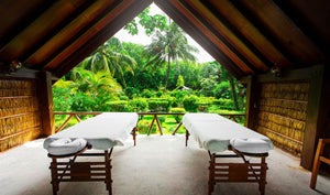 Two empty massage tables overlooking lush tropical forest
