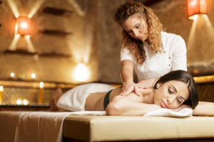Female client lies on a massage table receiving a massage treatment from a female therapist