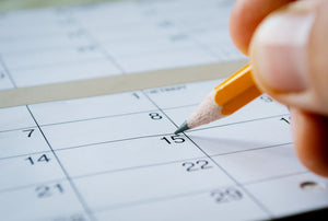 Massage therapist marking the date of the 15th with a pencil on a blank calendar with date squares as a reminder of an important day or to schedule an appointment
