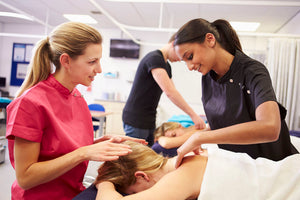 Teacher Helping Student Training To Become Massage Therapist