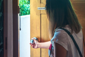 Woman grabbing door knob opening brown wooden door
