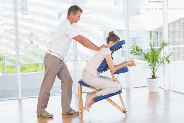 Woman having back massage in medical office from a male therapist wearing a polo shirt and loose slacks