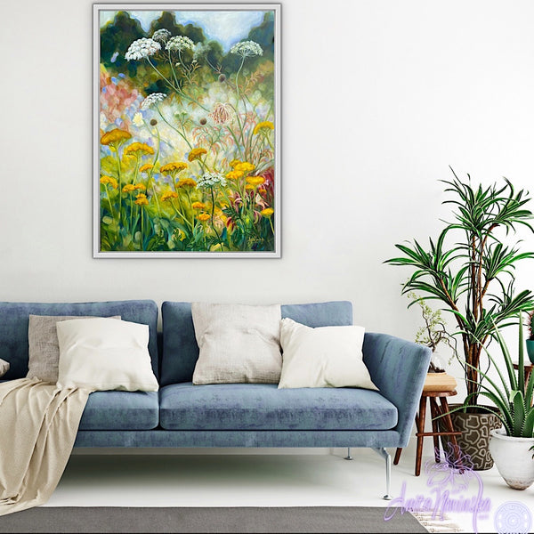 wild flower garden painting by anita nowinska in room with white walls & blue sofa. Yellow, gold, green colours