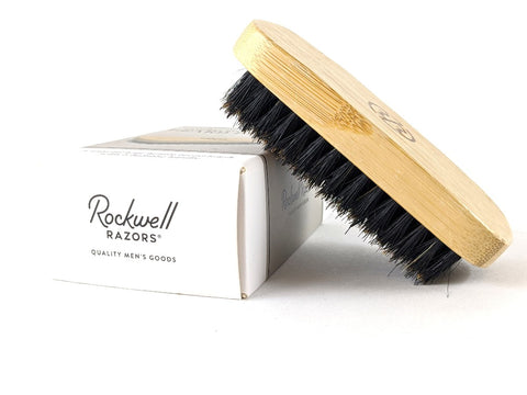 Wooden beard brush with black bristles on box.