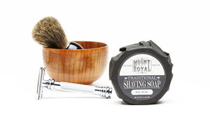 Bamboo container with brush behind a razor behind a black wrapped shaving soap.