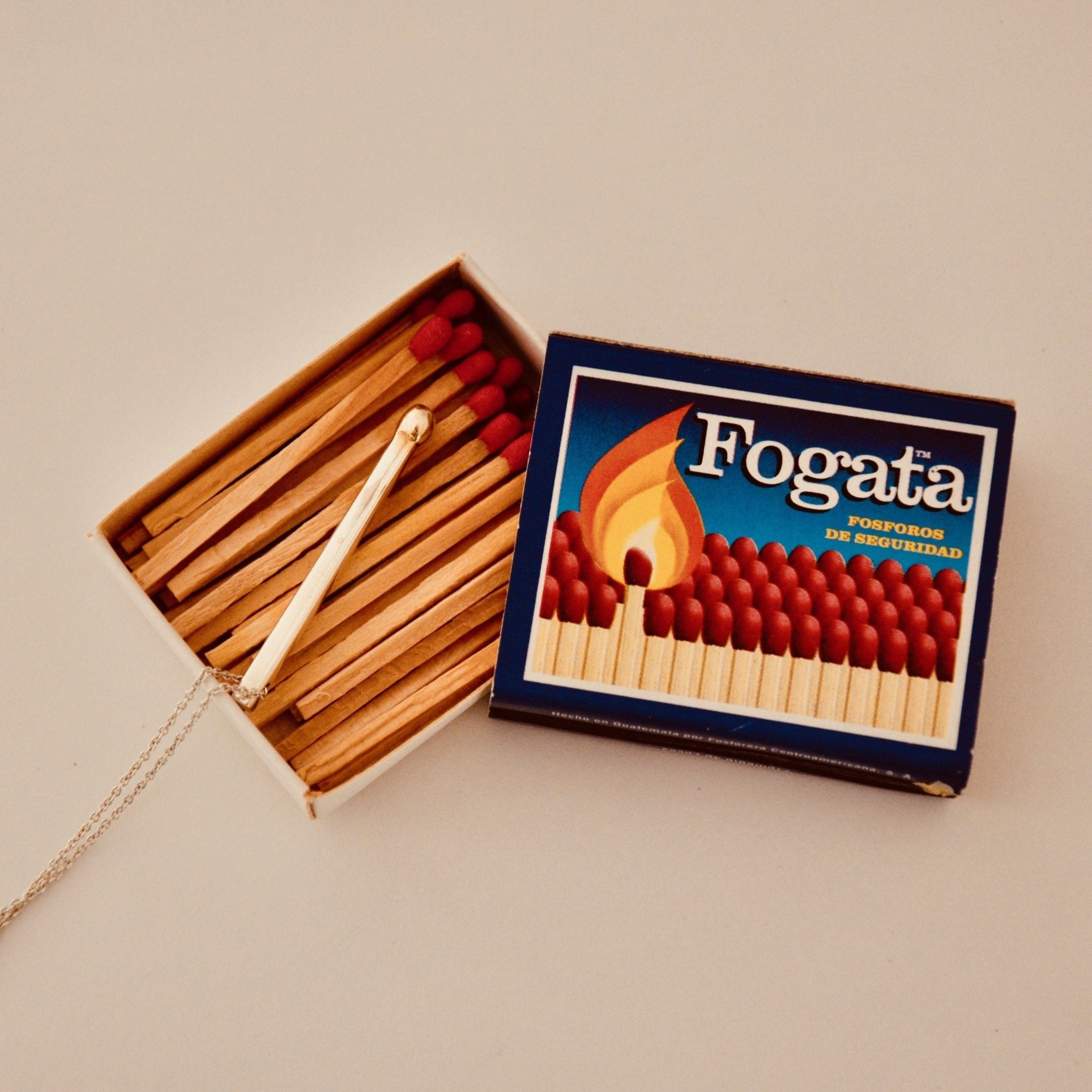 silver and gold necklace in the shape of a matchstick inside a matchbox