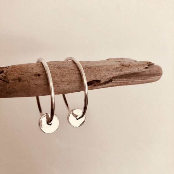 large thin silver hoop earrings with silver dangling cylinder hanging from driftwood