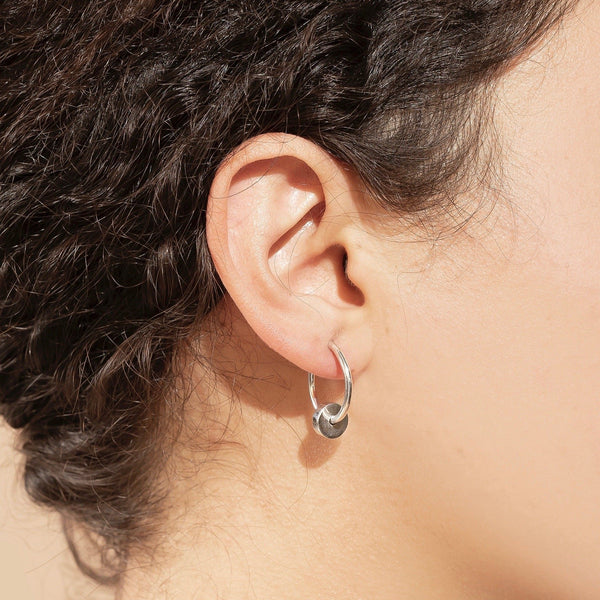 close up a woman wearing a small thin silver hoop earring with silver dangling cylinder