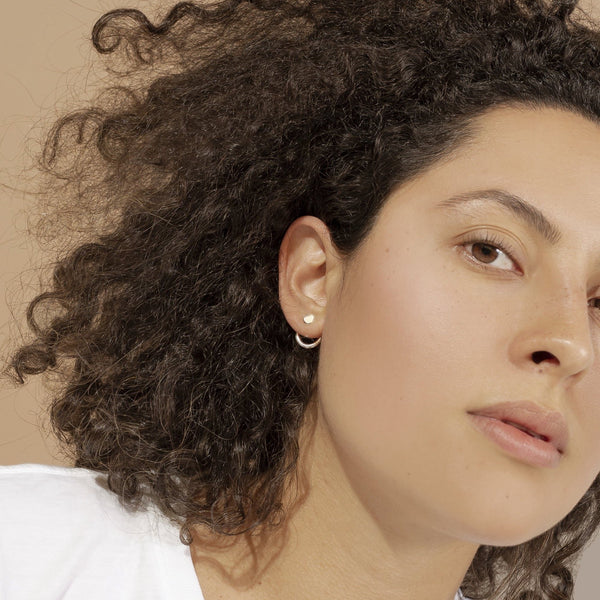 woman wearing small silver hoop earrings with silver studs