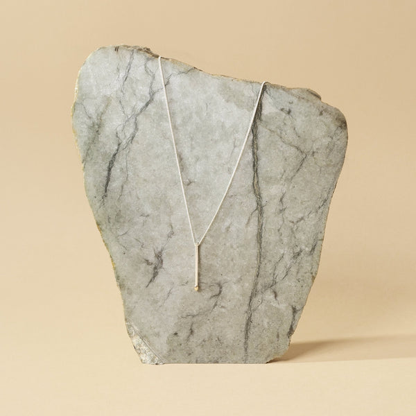 silver and gold necklace in the shape of a matchstick hanging on a jade stone
