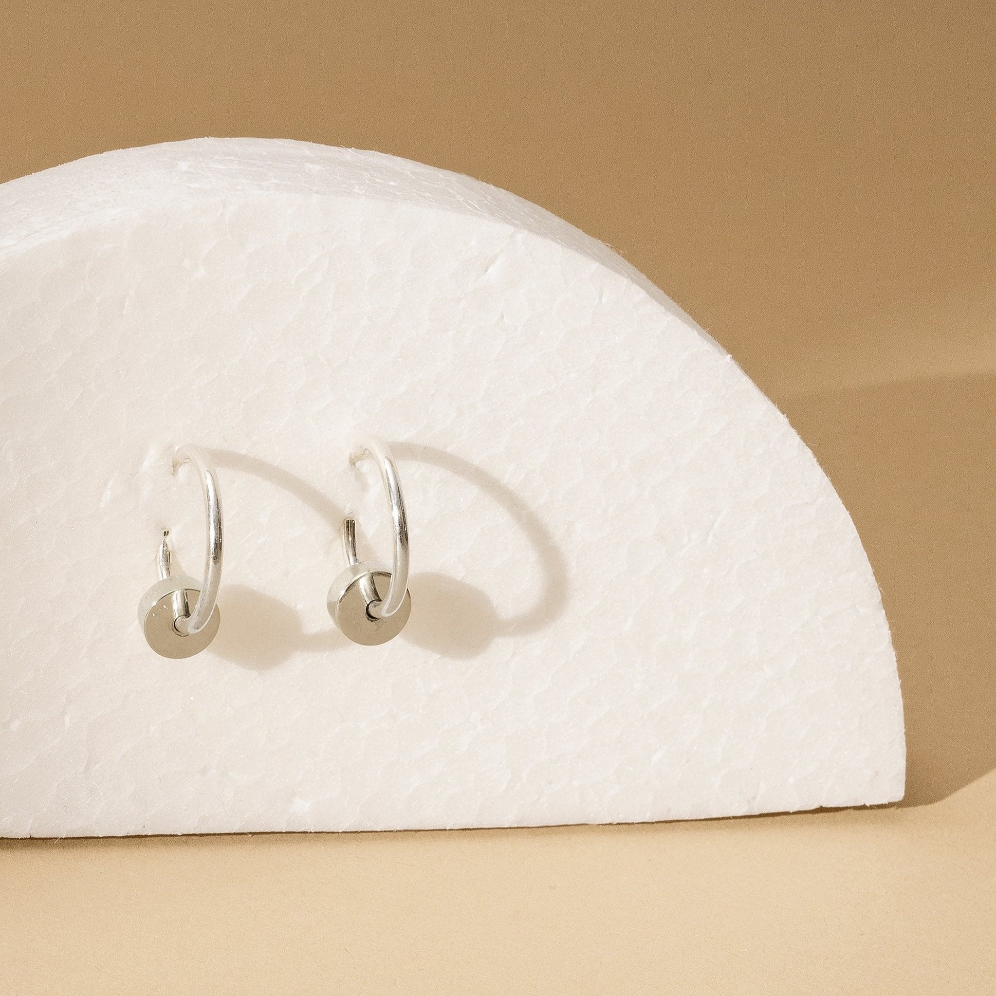 small thin silver hoop earrings with silver dangling cylinder hanging from white semi-circle