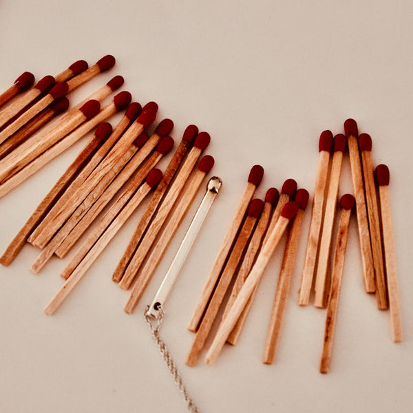 silver and gold necklace in the shape of a matchstick displayed next to real matches