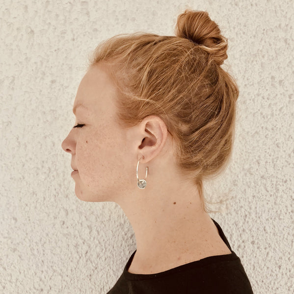 woman wearing large thin silver hoop earrings with a dangling cylinder