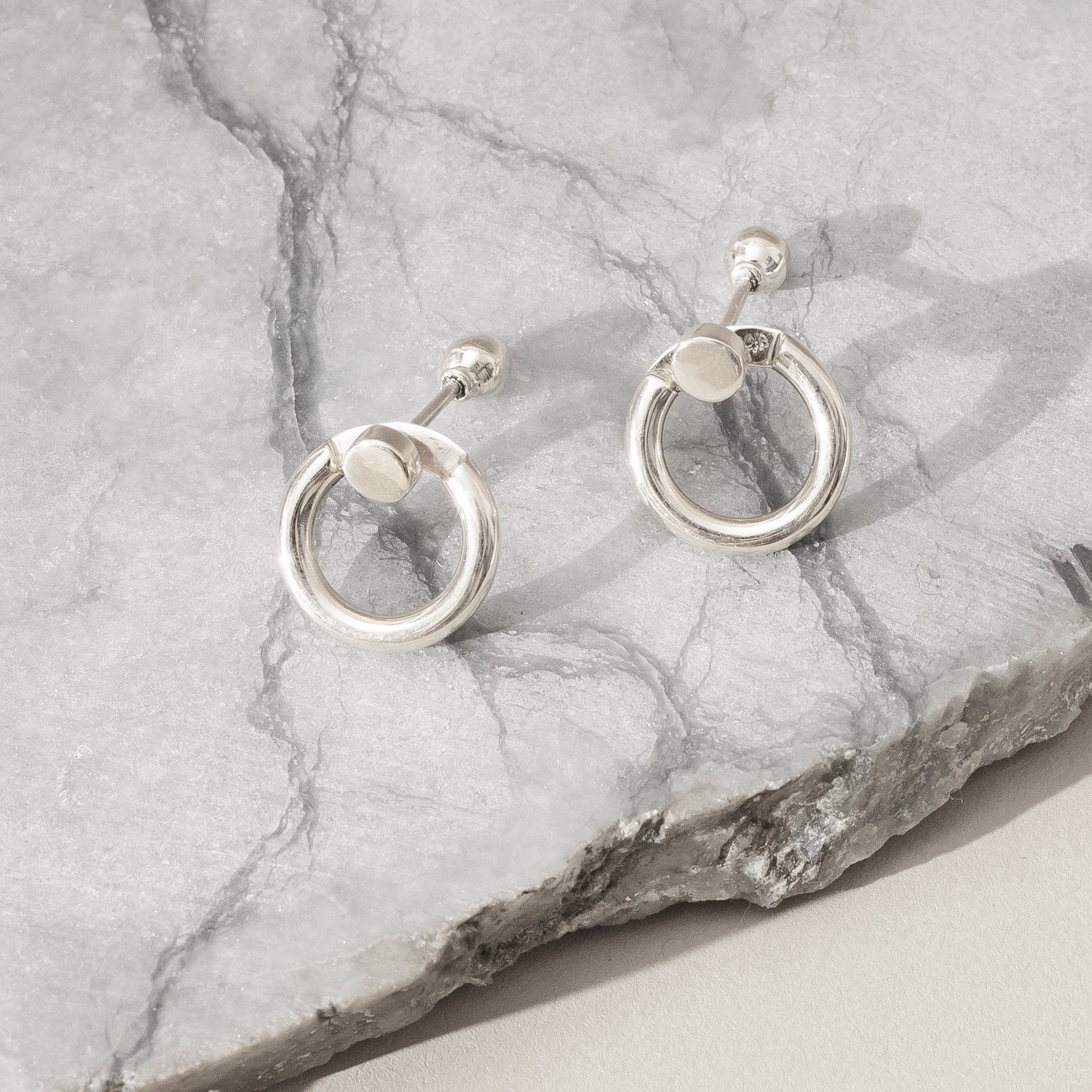 small silver hoop earrings with silver studs displayed on a jade stone