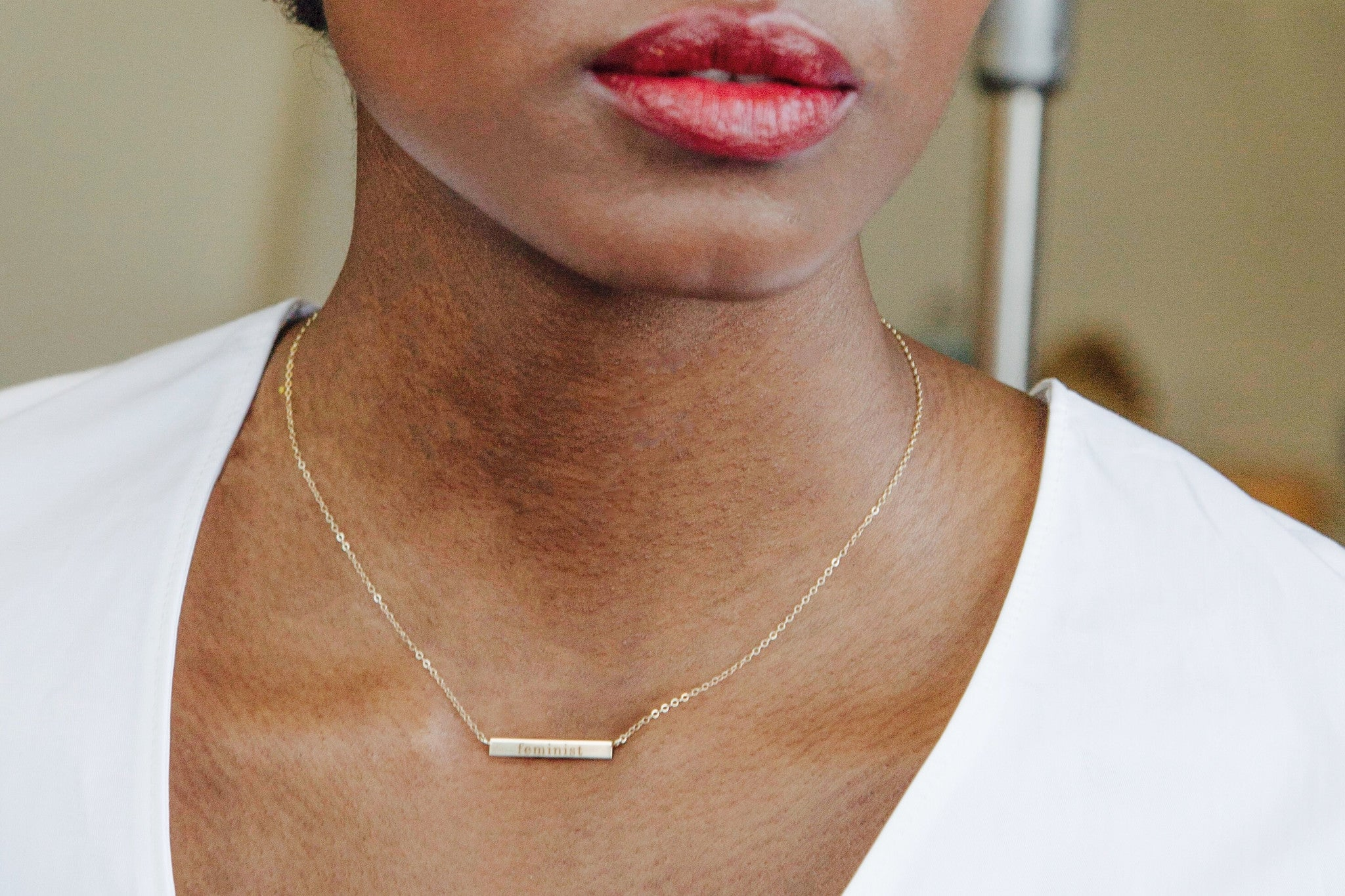 "14K Gold Bar Necklace with ""feminist"" engraving on model"