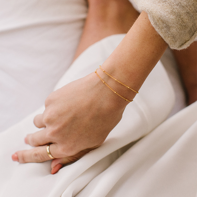 Dainty bracelet in satellite chain layered with a gold ring on a Made By Mary model.