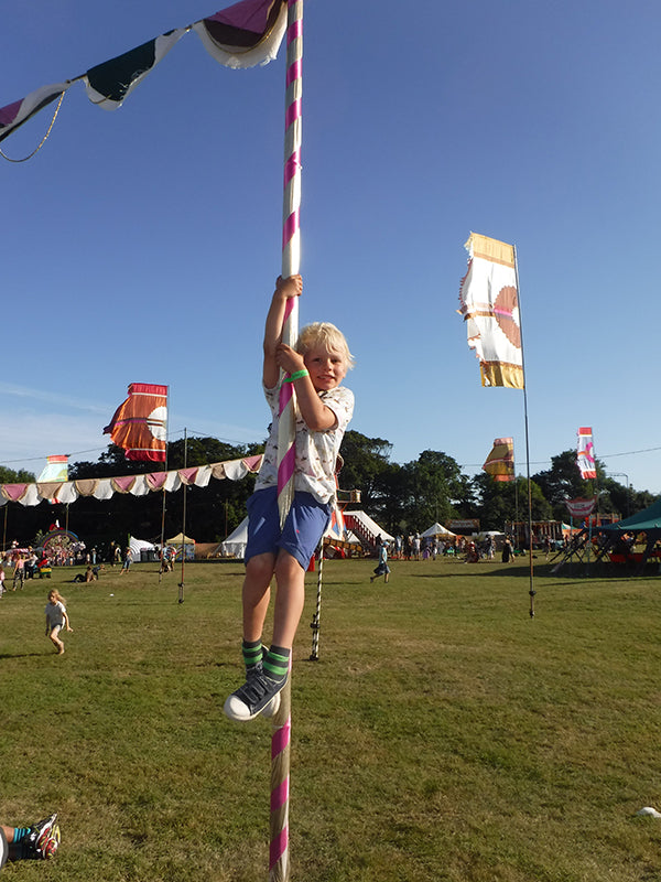 boy climbing pole at camp bestival