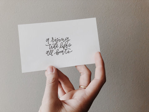 """A hand is holding up a white notecard against a plain wall - the index card reads """"a rising tide lifts all boats"""""""