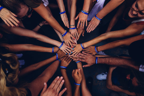 The image is centered on the hands from a large group huddle meeting together in the middle, the hands are stacked on top of one another in a unified teamwork building and fun activity.