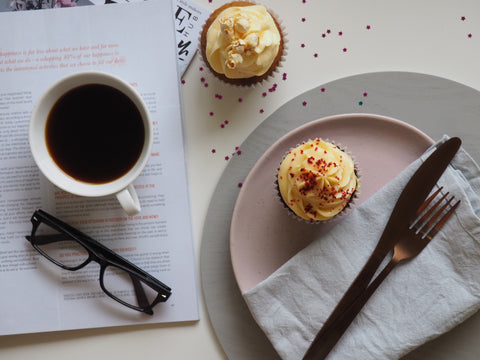 Two cupcakes and a mug of coffee are sitting on a desk, along with reading material, a plate, a fork and knife, and a pair of glasses.